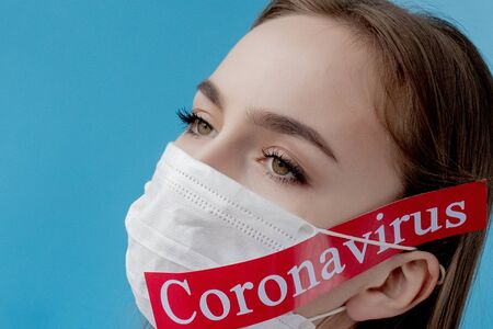 Doctor woman with surgical mask pointing to red paper with mesaage Coronavirus on blue background. World Health Organization WHO introduced new official name for Coronavirus disease named COVID-19.