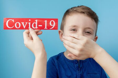 Little boy pointing to red paper with mesaage Coronavirus on blue background. World Health Organization WHO introduced new official name for Coronavirus disease named COVID-19.