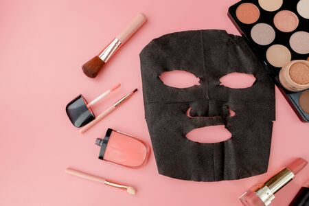 black cosmetic mask and makeup set on pink background with copy space.
