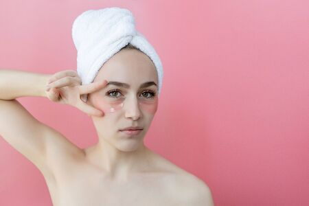 Portrait of Beauty Woman with Eye Patches on pink background. Woman Beauty Face with Mask under Eyes. Skin care, cosmetic product concept with copy space.