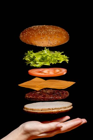 Flying ingredients burger or cheeseburger on a small wooden cutting board isolated on a dark background. Burger floating in the air above the table. Space for text.