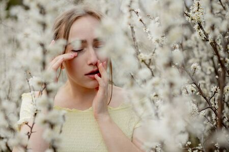 Young girl blowing nose and sneezing in tissue in front of blooming tree. Seasonal allergies affecting people. Beautiful lady has rhinitis.