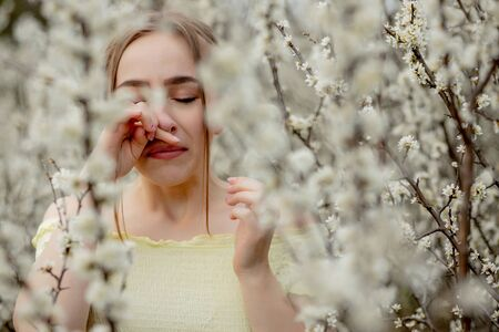 Young girl blowing nose and sneezing in tissue in front of blooming tree. Seasonal allergens affecting people. Beautiful lady has rhinitis.