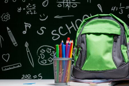 Education concept - green backpack, notebooks and school supplies on the background of the blackboard.