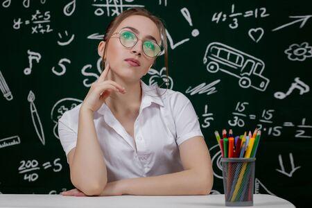 Young teacher is sitting near blackboard in classroom.