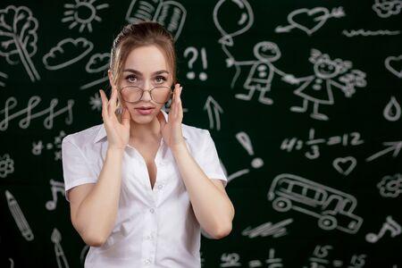 Young teacher is standing near blackboard in classroom.