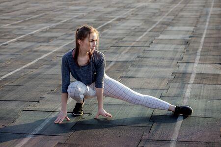 Female runner stretching legs on running track.
