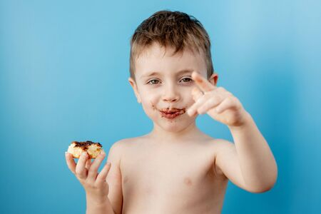 Little boy eating donut chocolate on blue background. Cute happy boy smeared with chocolate around his mouth. Child concept, tasty food for kids. Reklamní fotografie