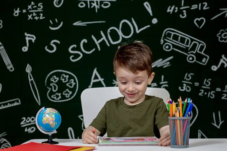 Cute child boy doing homework. Clever kid drawing at desk. Schoolboy. Elementary school student drawing at workplace. Kid enjoy learning. Home schooling. Back to school. Little boy at school lesson.