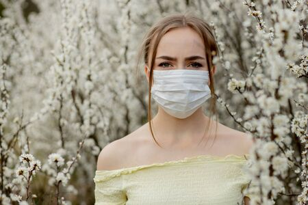 Girl in a medical mask. Girl in the spring among the blooming garden. A girl in a protective medical mask. Spring allergy concept.