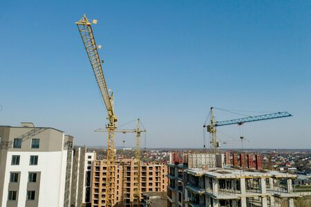 Construction and construction of high-rise buildings, the construction industry with working equipment and workers. View from above, from above. Background and texture.