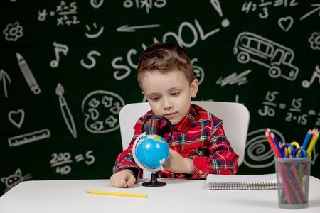 Cute clever boy is sitting at a desk with magnifying glass in hand. Child is reading a book with a blackboard on a background. Ready for school. Back to school.