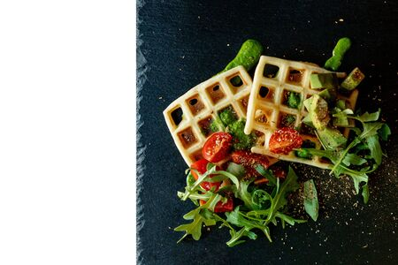 Fresh baked Belgian waffles with arugula, tomatoes and avocado on black a plate isolated on white background. Savory waffles. Breakfast concept. Healthy breakfast.