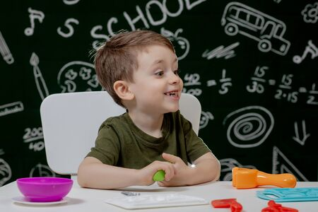 Cute little boy moulds from plasticine on table with a blackboard on a background. Ready for school. Home schooling. Back to school. Reklamní fotografie