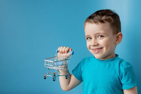 Boy in blue t-shirt is holding little cart for buying goods, products on blue background. Shopping and sale concept. Reklamní fotografie