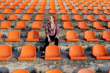 Happy woman standing in amongst the rows of empty seats at stadium cheering with her arms raised punching air.