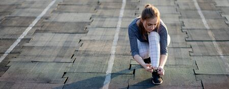 Female runner lacing her sneakers on a stadium running track. Healthy lifestyle. Reklamní fotografie