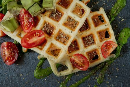 Fresh baked Belgian waffles with arugula, tomatoes and avocado on black a plate. Savory waffles. Breakfast concept. Healthy breakfast.