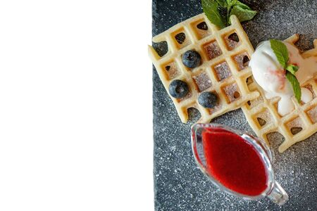 Fresh baked homemade classic Belgian waffles topped with icecream, fresh blueberries and mint isolated on white background, top down view. Savory waffles. Breakfast concept.