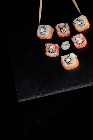 Philadelphia roll with salmon, cheese and cucumber on a black background. Sushi Philadelphia. Reklamní fotografie