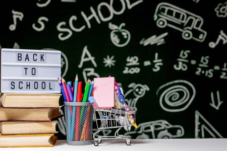 Back to school background with books, pencils and globe on white table on a green blackboard background Reklamní fotografie