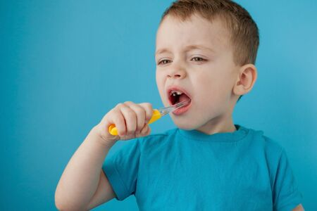 Little cute boy brushing his teeth on blue background. Banque d'images