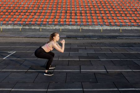 Female athlete preparing legs for cardio workout. Fitness runner doing warm-up routine. woman runner warm up outdoor. athlete stretching and warming up on a running track in a stadium.