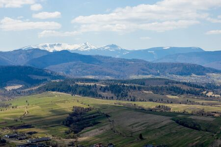 View of the Carpathian Mountains landscape in cloudy summer day. Mountain peaks, forests, fields and meadows, beautiful natural landscape.