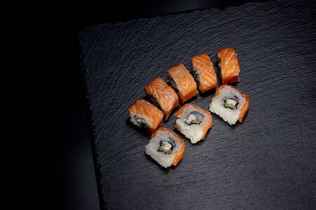 Close up delicious Japanese food sushi over dark background with copy space.