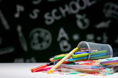 School background with stationery accessories. Books, globe, pencils and various office supplies lying on the desk on a green blackboard background. Reklamní fotografie