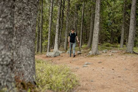 A man is a tourist in a pine forest with a backpack. A hiking trip through the forest. Pine reserve for tourist walks. A young man in a hike in the summer Reklamní fotografie