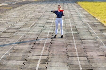 Young slim woman in sportswear doing squats exercise with rubber band on a black coated stadium track.