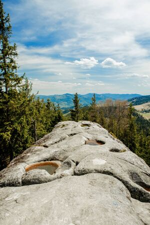 View from the mountain Written Stone on the mountain landscape of the Carpathians. Carpathian Mountains top view landscape ridge summer season dramatic weather time with cloudy blue sky background.