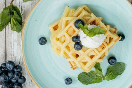 Fresh baked homemade classic Belgian waffles topped with icecream, fresh blueberries and mint on wooden background, top down view. Savory waffles. Breakfast concept.