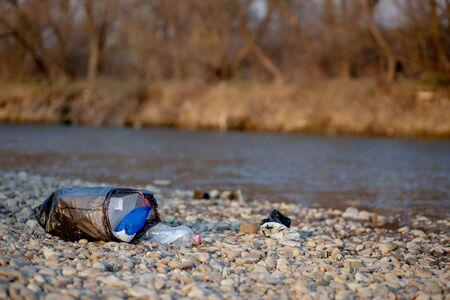 Garbage near the river. Environmental pollution shore.