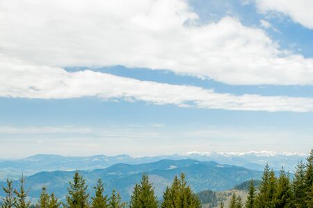Magnificent panoramic view the coniferous forest on the mighty Carpathians Mountains and beautiful blue sky background. Beauty of wild virgin Ukrainian nature. Peacefulness. View from the mountain handwritten stone on the Carpathian mountains.