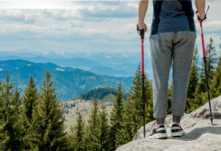 Young, carefree boy climbing up solid huge rocks, using poles to make it easy to reach the top, enjoying the view of natural wonders on the way.