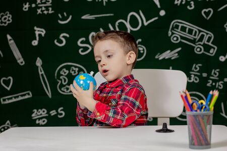 Portrait of cute little boy holding in hands small globe on blackboard background. Ready for school. Back to school