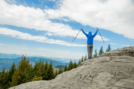 A mountain climber is high in the mountains against the sky, celebrating the victory, raising his hands up