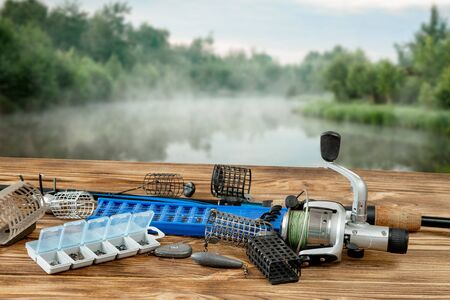 Fishing tackle and accessories on the table against the background of a lake. Selective Focus.