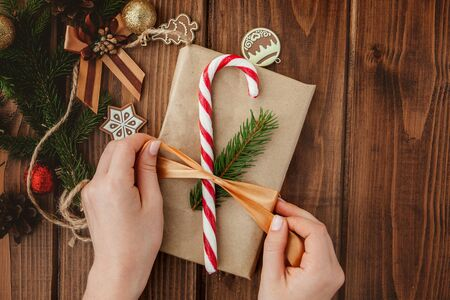 Woman s hands wrapping Christmas gift, close up. Unprepared christmas presents on wooden background with decor elements and items, top view. Christmas or New year DIY packing Concept