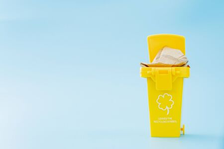 Large yellow trash can garbage bin with wheel, isolated on blue background. Stockfoto