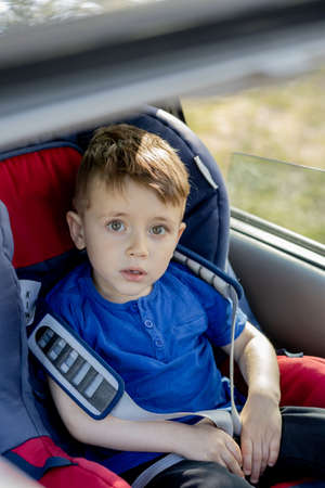 Portrait of cute toddler boy sitting in car seat. Child transportation safety.