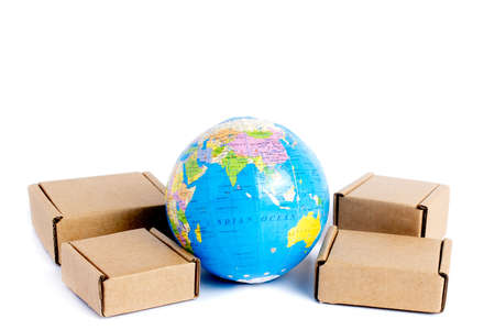 Earth globe is surrounded by boxes isolated on white background. Global business and international transportation of goods products. Shipping freight, world trade and economics. Distribution, import export. Commodity turnover.