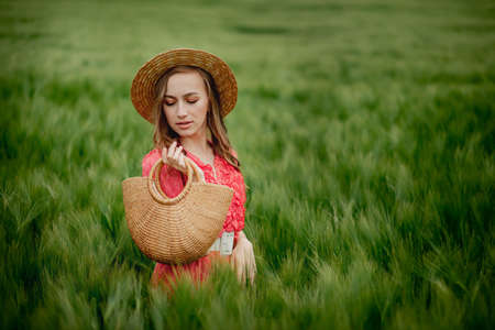Young woman in dress and hat in green field of barley in countryside. Stylish girl in rustic dress enjoying peaceful moment in grass in summer. Tranquil rural moment Archivio Fotografico
