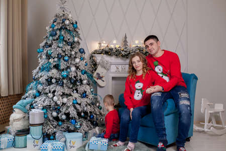 Happy family of three, young mother expecting a new baby, father and their little son near decorated Christmas tree.