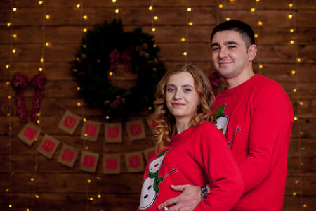 A pregnant woman and her husband in the studio. Pregnant couple. Husband hugging his pregnant wife. Christmas and New Year.