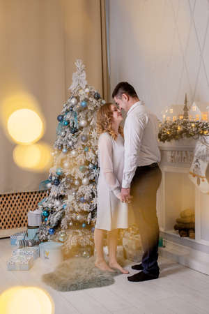 Close up of happy married couple bonding next to Christmas tree. Best Christmas gift. Young pregnant woman with her husband decorate the Christmas tree. A young loving couple in cozy sweaters. Archivio Fotografico