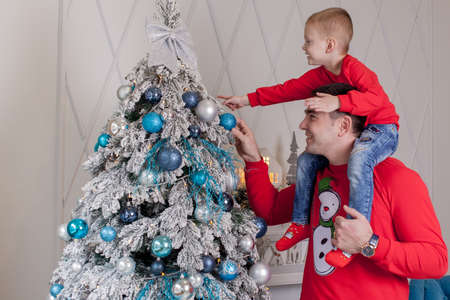 Happy Father and son enjoying decorating Christmas tree with Christmas balls and light garland preparing for celebrating winter holidays: Merry Christmas Eve and Happy New Year 2021. Family concept. Archivio Fotografico