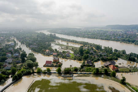 Climate change and the effects of global warming. Flooded village, farms and fields after heavy rains. Environmental natural disaster. Concept of global catastrophes in the world.